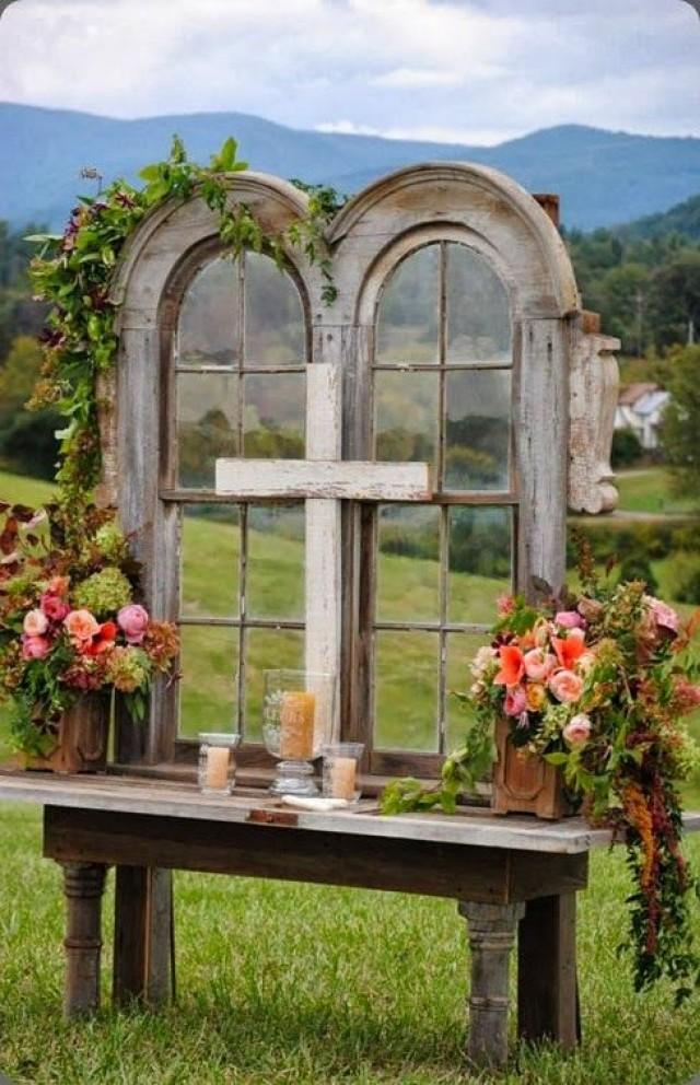 Use Of An Old Church Window Decorated With Leaf Vines And Flower Corsages Creates A Unique Rustic Look Items Like Wooden Cross Candles Too Add Country