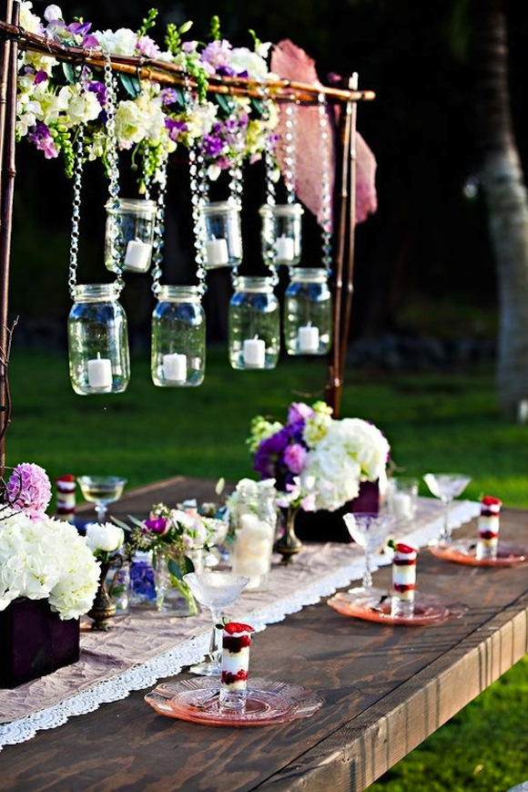decorating the rod or bar you use to hang the jars from with clusters of flowers is sure to wow your guests